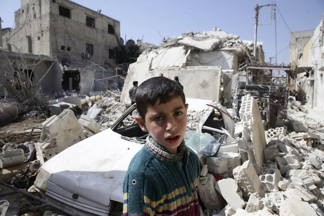 A boy looks on while residents inspect a damaged building in the rebel held besieged city of Douma, a suburb of Damascus